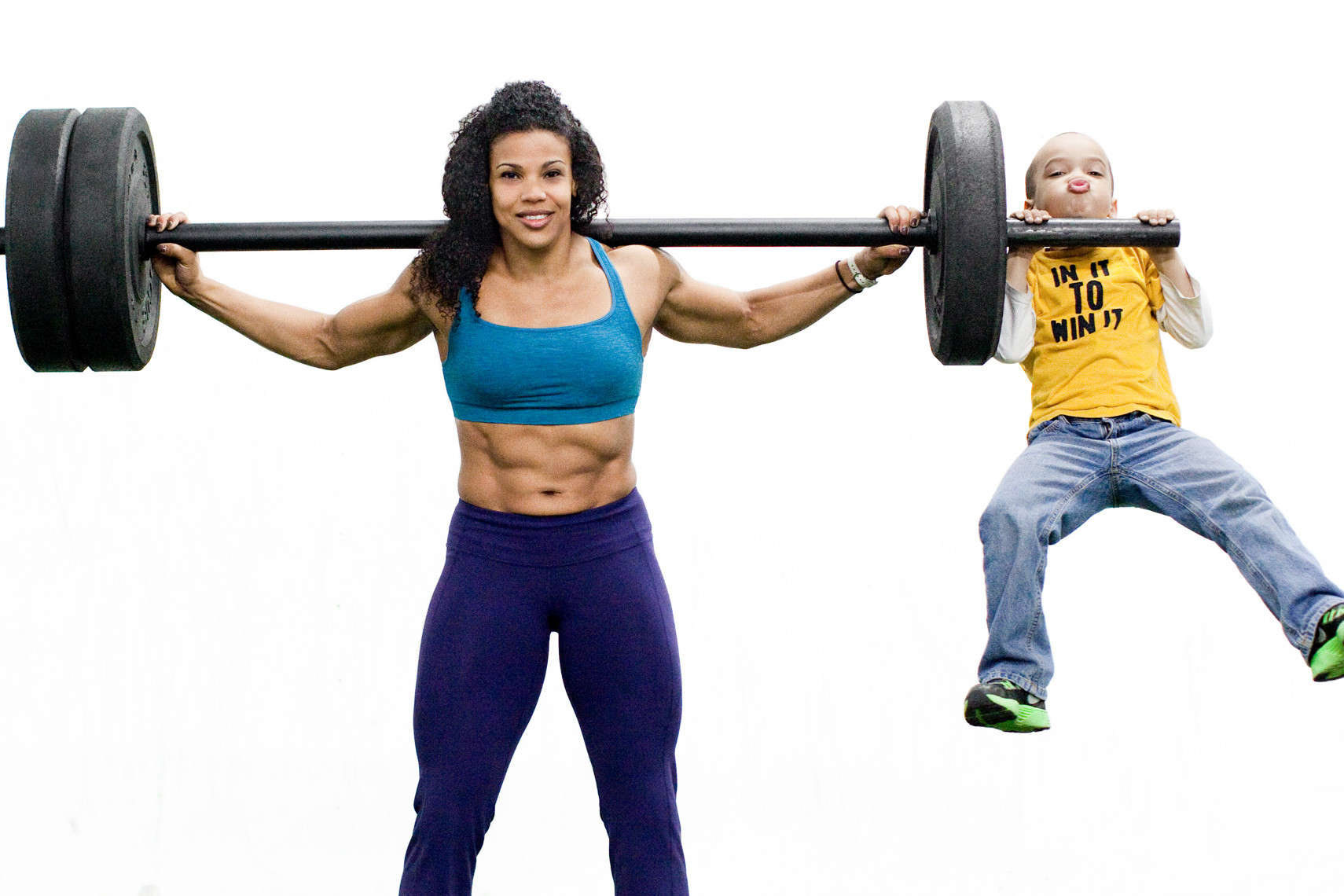 Los Angeles Sports Photography, Michael Brian, female, mother, Elisabeth Akinwale, Reebok Crossfit Games athlete, backsquat with son hanging on bar, Chicago, Sweat RX Magazine
