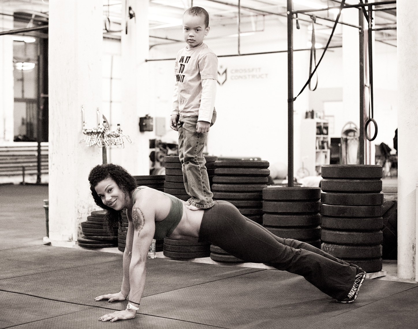 Los Angeles Sports Photography, Michael Brian, female, mother, Elisabeth Akinwale, Reebok Crossfit Games athlete, weighted pushup with son on back, Chicago, Sweat RX Magazine